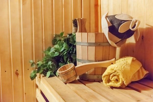 Szczegóły wnętrza sauna fińska łaźnia parowa z tradycyjnymi akcesoriami do sauny umywalka brzozowa miotła czapka filcowa