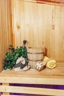 Szczegóły wnętrza sauna fińska łaźnia parowa z tradycyjnymi akcesoriami do sauny umywalka brzozowa miotła miarka filcowy kapelusz ręcznik. tradycyjna stara rosyjska łaźnia spa concept. relaksująca koncepcja kąpieli w wiejskiej wiosce