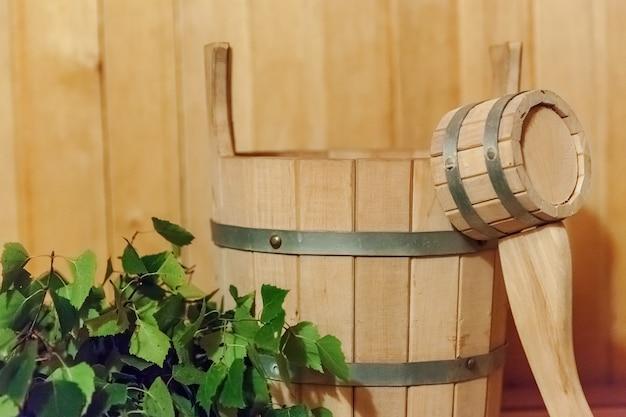 Szczegóły wnętrza sauna fińska łaźnia parowa z tradycyjnymi akcesoriami do sauny umywalka brzozowa miotła miotełkowa.