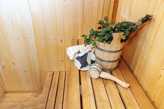 Szczegóły wnętrza sauna fińska łaźnia parowa z tradycyjnymi akcesoriami do sauny umywalka brzozowa miotła miotła czapka filcowa.