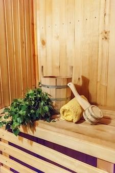 Szczegóły wnętrza sauna fińska łaźnia parowa z tradycyjnymi akcesoriami do sauny umywalka brzozowy ręcznik do miotły.