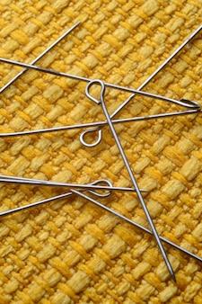 Szczegóły żółtych szpilek do szycia na żółtym tle tekstury.7
