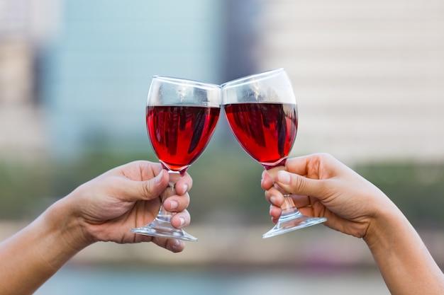 Szczęk szkła czerwone wino w rękach na naturze zaświecają tło