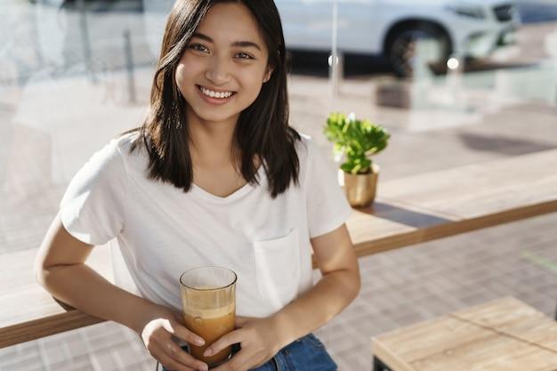 Szczelnie-do góry azjatykcia kobieta uśmiecha się szczęśliwie i szuka aparatu