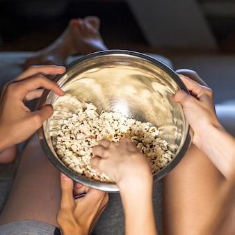 Szczelnie-do góry ludzi z miską popcornu w pomieszczeniu