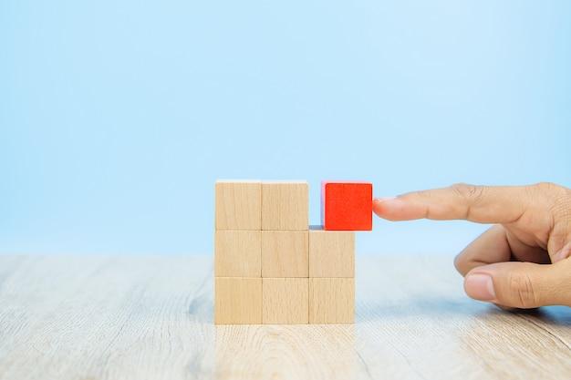 Szczelnie-do góry rękę wybierz drewniany klocek w kształcie sześcianu ułożony bez grafiki.