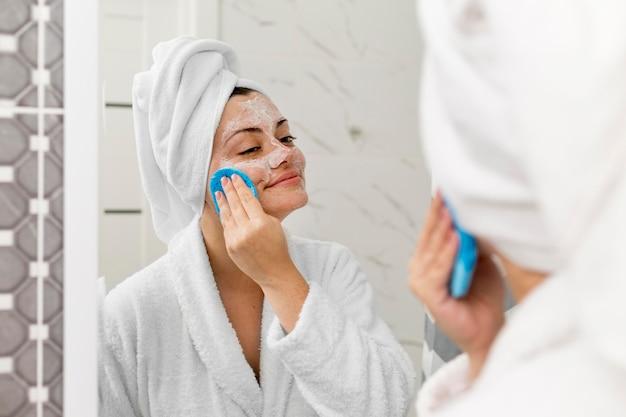 Szczelnie-do góry uśmiechnięta kobieta czyszczenia twarzy