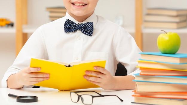 Szczelnie-do góry uśmiechnięty chłopiec czytanie