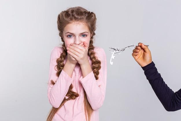 Szczelnie kryjąca. boi się, że długowłosa dziewczyna zamyka usta obiema rękami, mając słuchawki przy twarzy