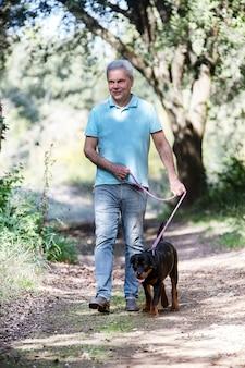 Szczeniak rottweiler i właścicielka w naturze jesienią