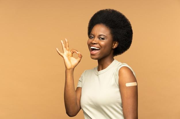 Szczepienie covid szczęśliwa czarna kobieta z bandażem po szczepionce na koronawirusa pokazująca dobry gest