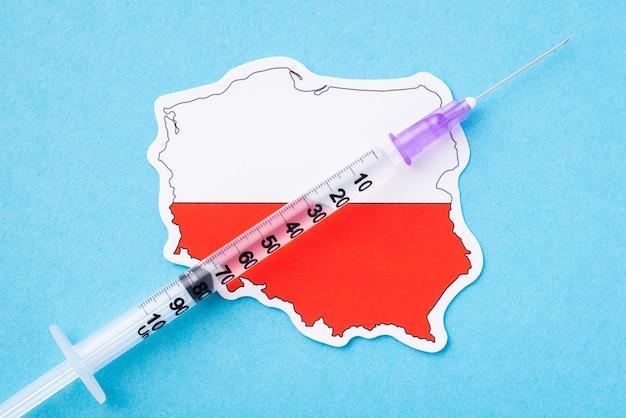 Szczepienie koronawirusowe w polsce. strzykawka z płynem na mapie polski