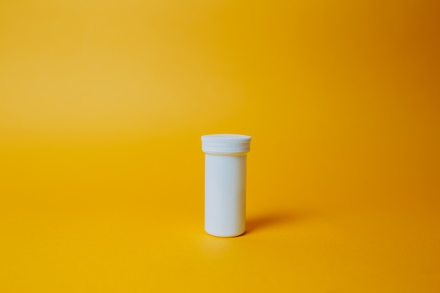 Szczepionka coronavirus w białym słoju medycyny na pomarańczowym tle. tabletki do utwardzania covid-19. pojedyncza biała puszka z lekiem.