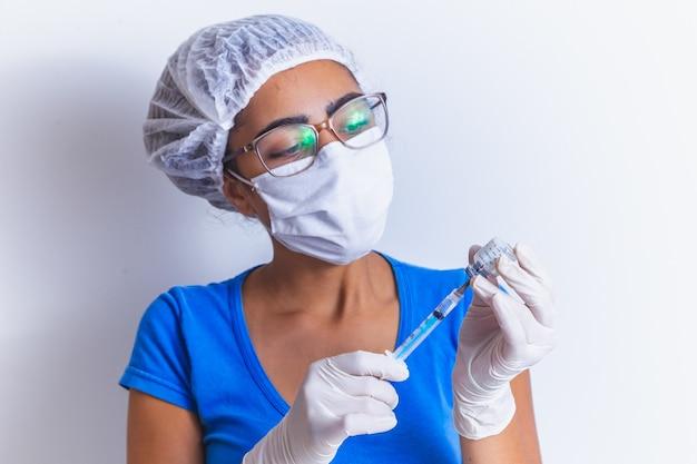 Szczepionka covid-19 w rękach badacza, lekarka trzyma strzykawkę i butelkę ze szczepionką na koronawirusa. koncepcja leczenia koronawirusa, iniekcji, zastrzyku i badania klinicznego podczas pandemii.