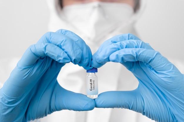 Szczepionka covid-19 w rękach lekarzy lub pielęgniarek w postaci serca w niebieskich gumowych rękawiczkach. zapobieganie sars-cov-2 lub covid-19.