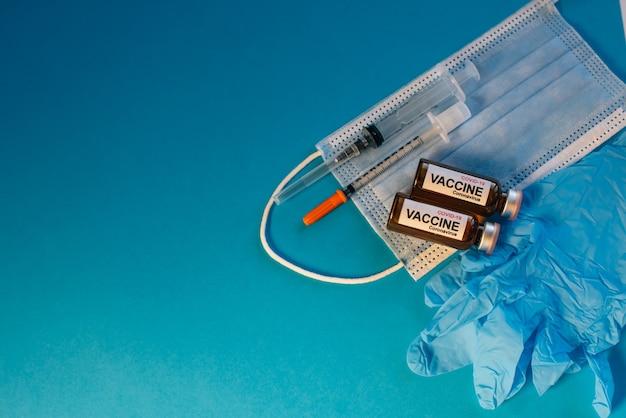 Szczepionka koronawirusowa w butelkach na niebieskim tle z miejsca na kopię.