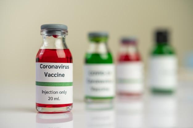 Szczepionka przeciwko covid-19 jest w kolorze czerwonym i zielonym w butelkach umieszczonych na podłodze.