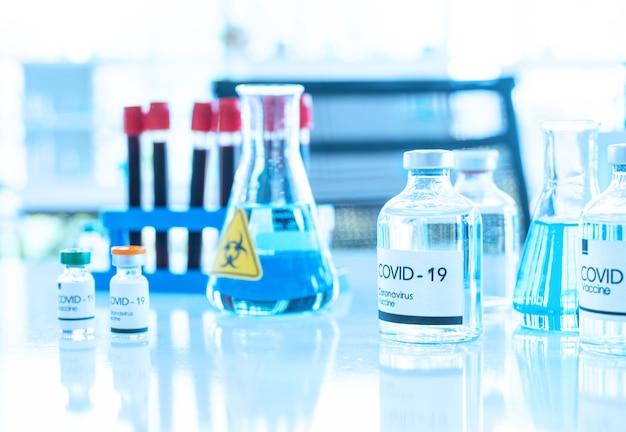 Szczepionka w fiolce w teście na kolanach stołowych. koncepcja szczepień.