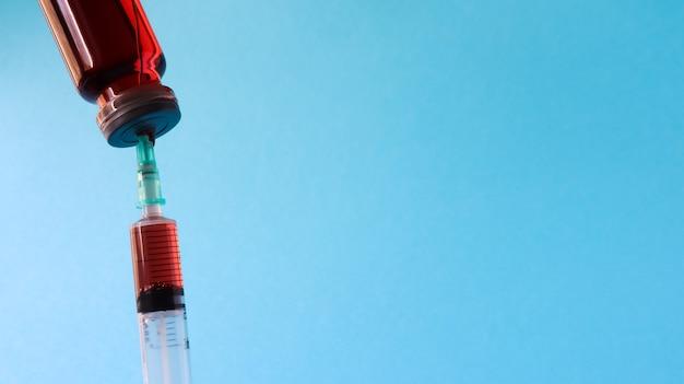 Szczepionki przeciw grypie i pandemii koronawirusa, strzykawka i fiolka z czerwonym płynem na niebieskim tle. koncepcja medyczna, wstrzyknięcie podskórne, leczenie choroby. skopiuj miejsce na tekst lub logo.
