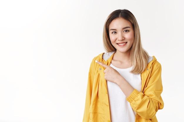 Szczera delikatna kobieca azjatycka młoda blond dziewczyna sugeruje fajną kopię miejsca promo wskazujący lewy palec wskazujący uśmiechnięty ząb troskliwy delikatną rozmowę omówić niesamowitą reklamę, biała ściana