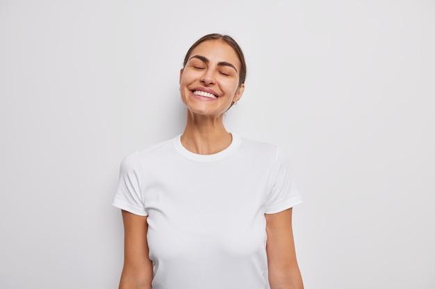 Szczera i pozytywna europejka o ciemnych włosach ma zamknięte oczy, szeroko uśmiecha się i pokazuje białe zęby, wyobraża sobie coś dobrze ubranego w zwyczajną koszulkę pozuje w pomieszczeniu