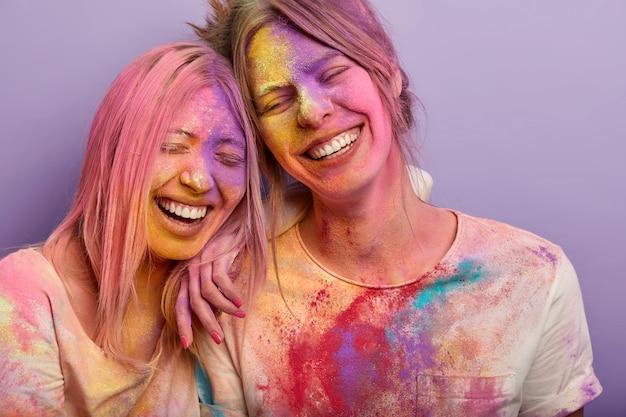Szczera koncepcja emocji i uczuć. śmieszne dwie koleżanki pochylają się do siebie, mają szerokie uśmiechy, kolorowe, brudne twarze, poplamione ubrania, uczestniczą w festiwalu holi