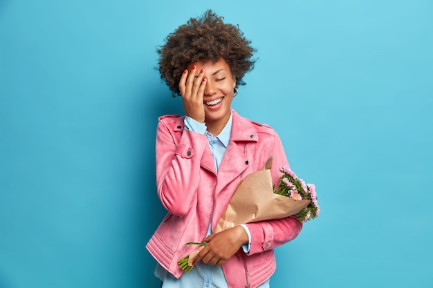 Szczera pozytywna kobieta ubrana w modne ubrania czuje się bardzo szczęśliwa, gdy otrzymuje bukiet kwiatów od ukochanej osoby, która sprawia, że twarz dłoni odizolowana jest na niebieskiej ścianie