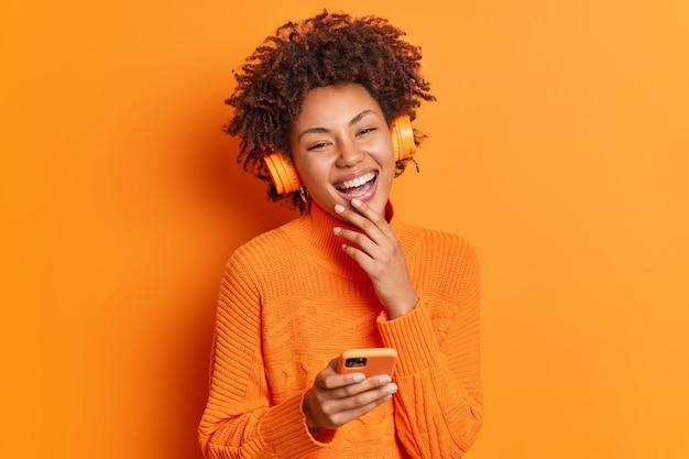 Szczera pozytywna młoda kobieta z kręconymi włosami, szeroko uśmiechnięta, nosi słuchawki stereo, słucha ulubionej muzyki z playlisty, trzyma nowoczesny smartfon
