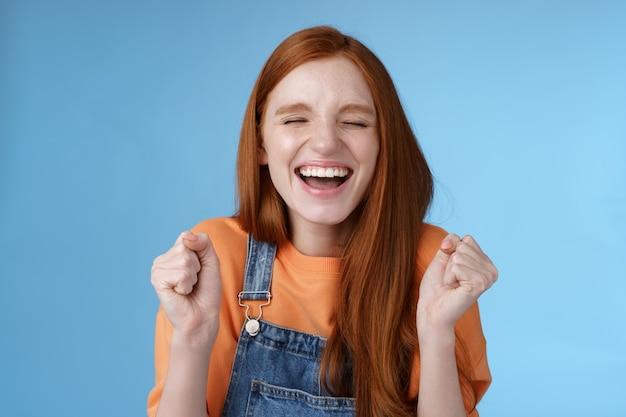 Szczera radość radosna rudowłosa dziewczyna zamknij oczy szeroko uśmiechnięta powiedz tak macha zaciśniętymi pięściami radośnie świętuje spełnienie marzeń uniwersytetu wygrywająca nagrodę triumfująca radośnie niebieskie tło