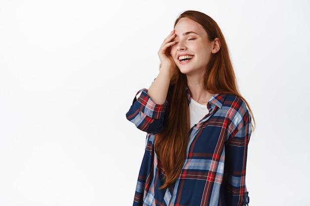 Szczera szczęśliwa ruda dziewczyna, śmiejąc się i uśmiechając białe zęby stojąc na białym.