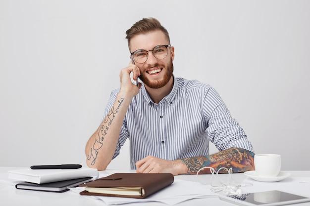 Szczere ujęcie modnego wytatuowanego mężczyzny w koszuli z podwiniętymi rękawami i okrągłymi okularami