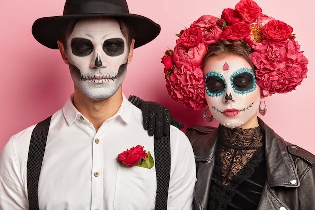 Szczere ujęcie spokojnej kobiety i mężczyzny zombie z zamkniętymi oczami, makijażu artystycznego, tradycyjnych strojów świątecznych, świętowania dnia śmierci, przerażającego spojrzenia, odizolowane na różowym tle.