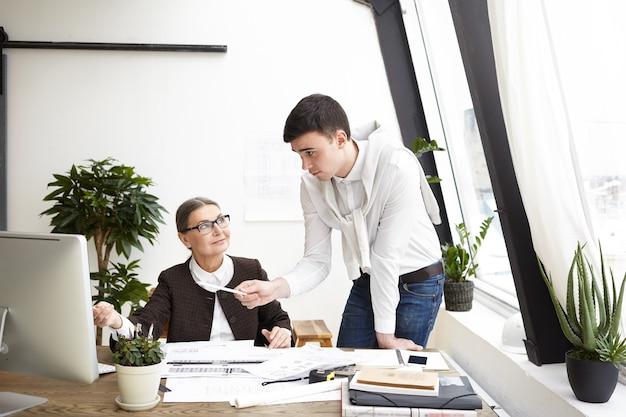 Szczere ujęcie szczęśliwej architektki w średnim wieku pracującej w biurze z młodym kolegą, który dzieli się kreatywnymi pomysłami i świeżym spojrzeniem na projekt budowy, wskazując palcem na ekran komputera