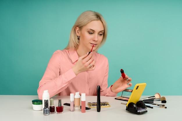 Szczere ujęcie uroczej młodej blogerki rasy kaukaskiej prezentującej produkty kosmetyczne i transmitującej wideo na żywo do sieci społecznościowej, używając błyszczyka podczas nagrywania codziennego samouczka makijażu