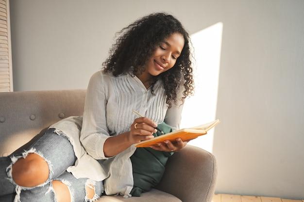 Szczere ujęcie uroczej ślicznej dziewczyny o wyglądzie mieszanej rasy, uśmiechającej się podczas pisania wierszy, zakochanej, dzielącej się swoimi przemyśleniami i sekretami w dzienniku. koncepcja ludzi, stylu życia i wypoczynku