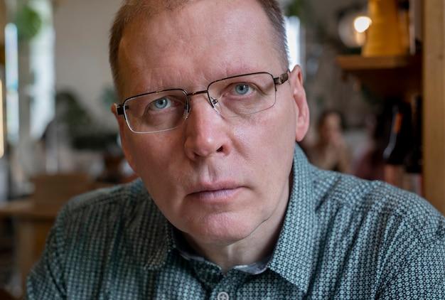 Szczery dojrzały mężczyzna w okularach patrzący poważnie na kamerę z prawdziwymi emocjami uwagi lub strachu.