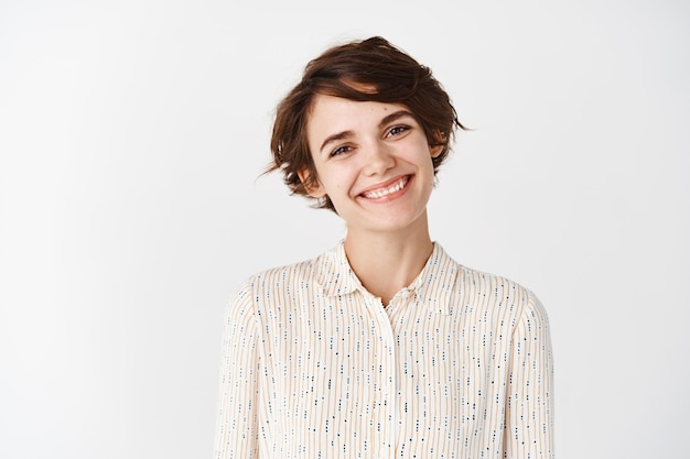 Szczery portret młodej pięknej kobiety uśmiechniętej szczęśliwie wyglądającej przyjaźnie, stojącej na białej ścianie