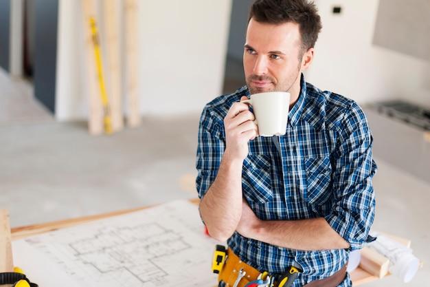 Szczery pracownik budowlany relaksuje przy filiżance kawy