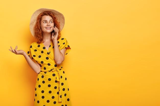 Szczery ruda kobieta pozuje w żółtej sukience polka i słomkowym kapeluszu