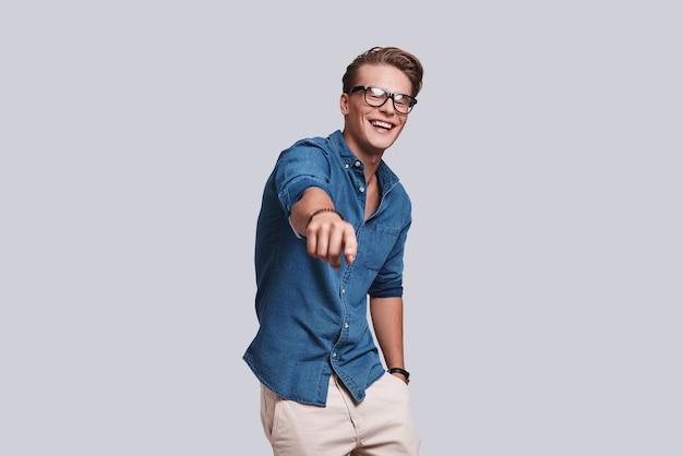 Szczery śmiech. przystojny młody mężczyzna wskazujący na ciebie i uśmiechający się stojąc na szarym tle