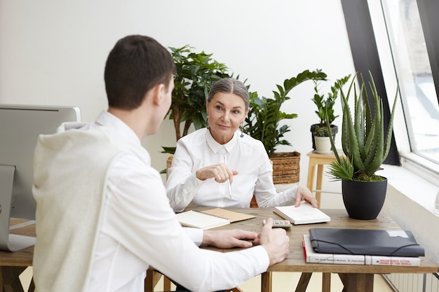 Szczery strzał atrakcyjne, pewność pracodawcy płci żeńskiej w średnim wieku siedzi przy biurku z zeszytem, robiąc notatki podczas rozmowy kwalifikacyjnej z potencjalnym nierozpoznawalnym młodym kandydatem płci męskiej. efekt filmu