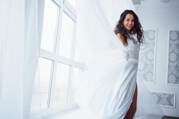 Szczery uśmiech. piękna kobieta w białej sukni stoi w białym pokoju ze światłem dziennym przez okna