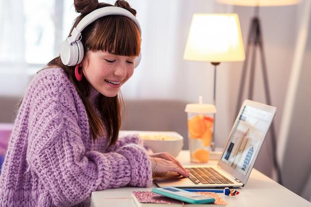 Szczery uśmiech. zadowolona mała kobieta słuchająca muzyki, patrząc na swój telefon