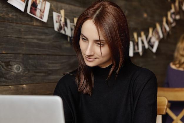 Szczery widok atrakcyjnej brunetki tłumaczki w czarnej sukience za pomocą wifi w kawiarni