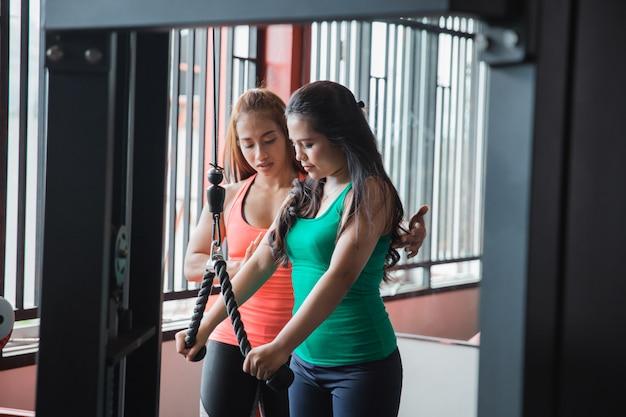 Szczery widok ćwiczy triceps pushdown z trai młoda kobieta