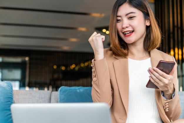 Szczęście azjatyckich przedsiębiorców świętuje, sprawdzając cel sukcesu za pomocą laptopa i telefonu komórkowego w nowoczesnym biurze lub coworkingu, portfela pieniędzy technologii i płatności online