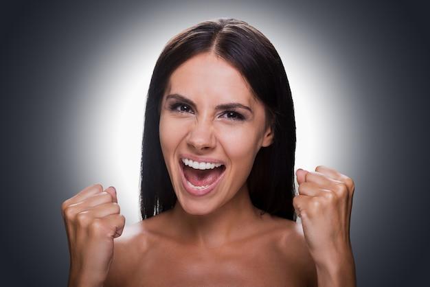 Szczęście bez granic. portret szczęśliwej młodej kobiety bez koszuli patrząc na kamerę i gestykulując stojąc na szarym tle