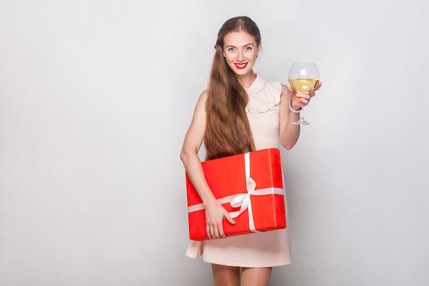 Szczęście blond kobieta w czerwonej czapce trzyma kieliszek do szampana i pudełko, patrząc na kamery i ząb uśmiechnięty. strzał studio. szare tło