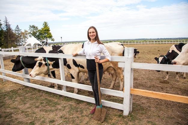 Szczęście dziewczyna karmienia krów na farmie. młoda dorosła dziewczyna z piegowatymi jesienią karmią krowę na wiejskim polu i bawią się ze zwierzętami, przyjaźń z krową. zabawa na wsi. na wolnym powietrzu