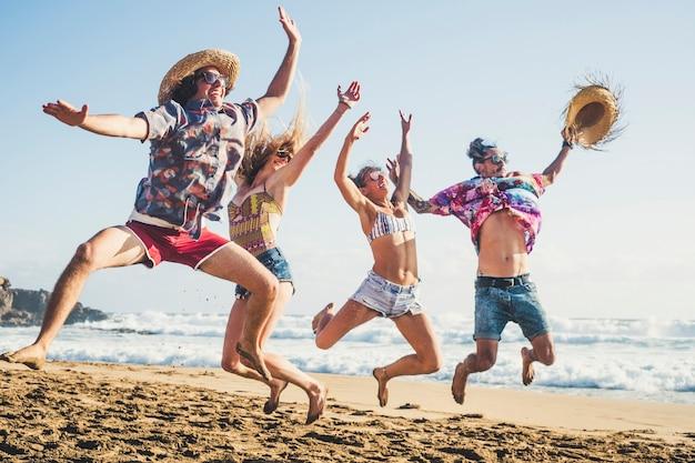 Szczęście i młodzi ludzie bawią się razem w przyjaźni na ebach na letnie wakacje, skacząc jak szaleni i śmiejąc się z błękitnym morzem i niebem w tle